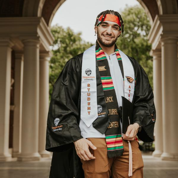 Picture of Adam in his gown wearing all of his stoles and holding his cap